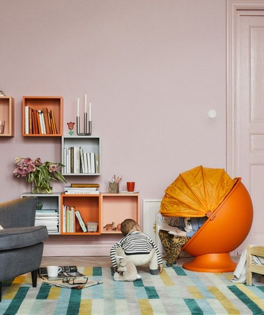 A Colorful Living Room With A Kids Orange Egg Chair And Two