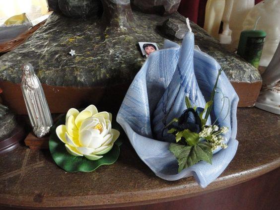 Imagem sacra, biscuit em forma de flor vitória régia, e origami em tecido na tonalidade azul.