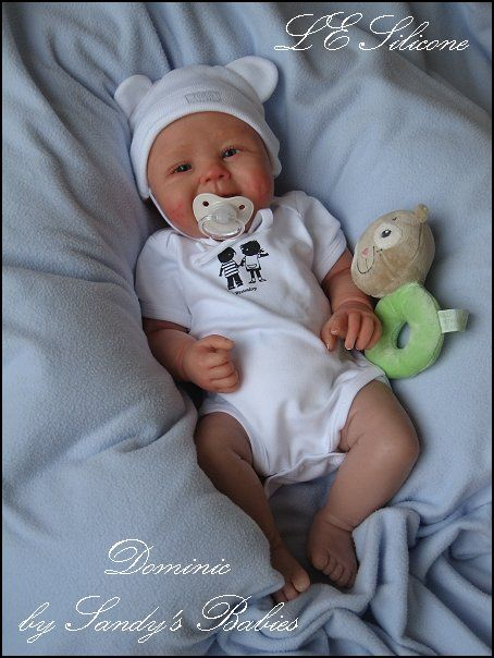 Dominic. Reborn doll. There's a smile behind that pacifier!