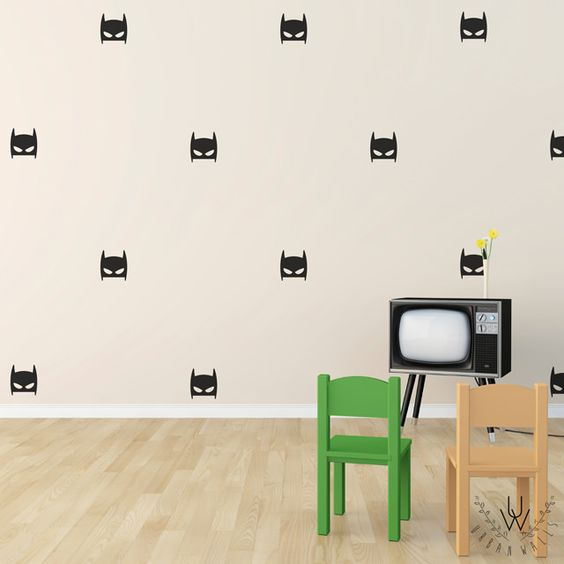 Black superhero mask wall stickers equally spaced as a pattern on a beige wall. Each superhero mask has two eyes and two points coming out of the top of the mask. In front there is a black TV and two small plastic chairs.