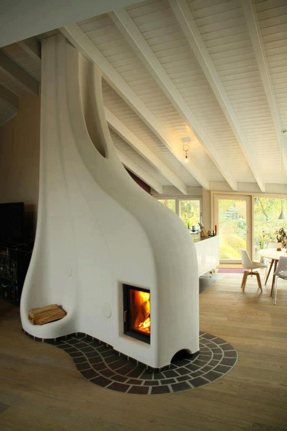 Here's a cool heater to warm you up as winter approaches. The fireplace is surrounded by sculpted cob - a mixture of clay, sand & straw - that absorbs the heat from the fire and stays warm long after the fire is done burning. Much more efficient than a regular fireplace (which can have a net cooling effect).