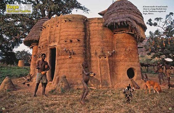 A house made of mud stands close to a large Baobab tree in the Tamberma region of Togo.