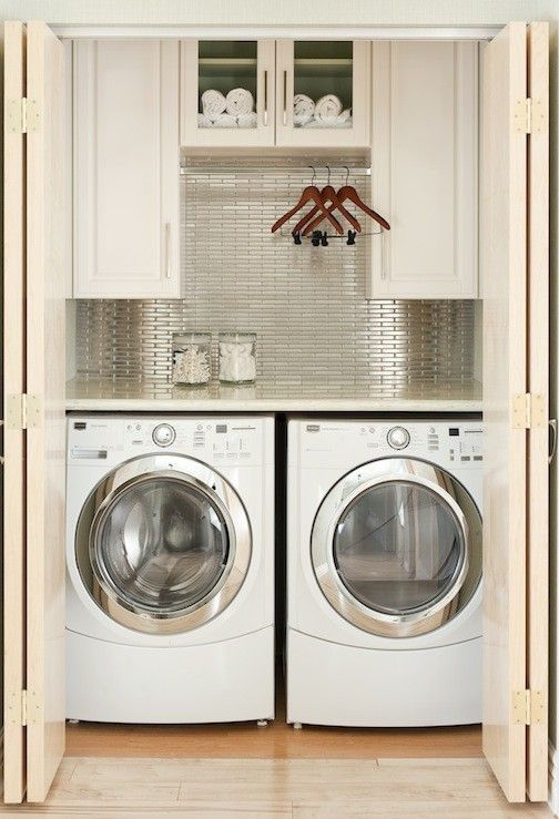 Laundry room closet  Likes:  1. White Cabinets for Storage  2. Folding Counter  3. Hanging Space for Clothes  4. Folding Doors  5. Idea of a backsplash in the laundry room