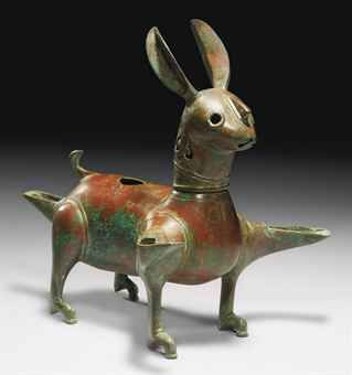 A RARE KHORASSAN BRONZE LAMP IN THE FORM OF A RABBIT  NORTH EAST IRAN, 12TH CENTURY  The rabbit stylistically formed with long ears, a pronounced nose, and short recurving tail, with two spouts issuing from the forelegs, and one beneath the tail, the back of the head with a band of openwork geometric and palmette design, a drop shaped hole to the back, the head separate and joined with a bayonet joint, some areas of corrosion, the majority of the surface with a rich red patina,  10in. high
