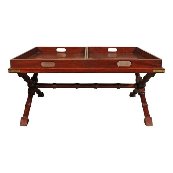 """This stylish coffee table is made from lustrous cherry wood and features two removable trays. The x-base has bamboo details and the corners have brass ornamentation. The trays have minor water stains.  The piece has minor scratches throughout. Each tray measures W 22"""" D 32.25"""" H 2.75"""""""