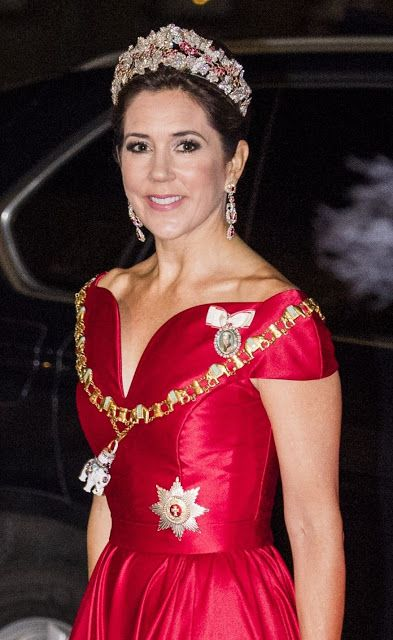 Crown Princess Mary of Denmark stunning in a shoulderless crimson gown which nipped in at the waist and featured a sweetheart neckline, top off with a glittering Ruby Parure tiara and a matching pair of diamond and ruby earrings, as she attended a traditional New Year's reception in Copenhagen on January 1, 2018