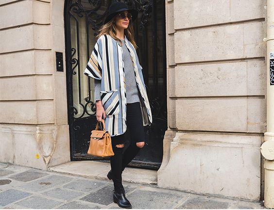 Look inspiração para usar poncho. A Sister Mari Cassou veste poncho listrado Mixed, tricot cinza mescla, jeans destroyed preto, botas pretas, chapéu preto, óculos redondinho e bolsa marrom.