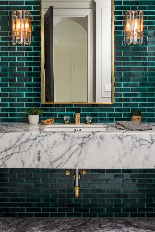 Art Deco Glass Sconces Mounted Against Emerald Green Subway Tiles Are Fixed On Either Side Of A Brass M Green Tile Bathroom Green Subway Tile White Marble Sink