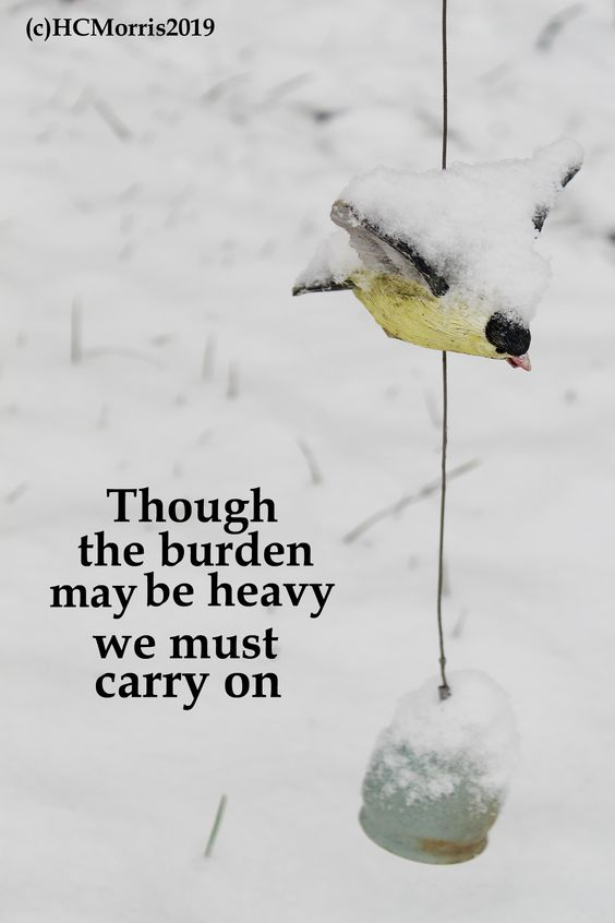 a bird wind chime with snow and words