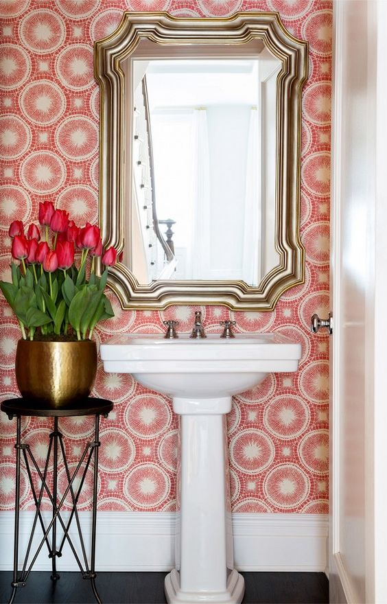 Red and white wallpaper with big bunch of pink tulips and a gold mirror in the bathroom: