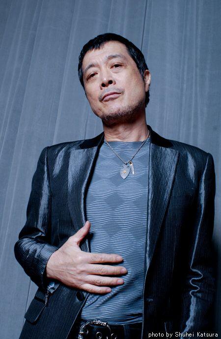 黒いジャケットを着て見下ろしている矢沢永吉の画像