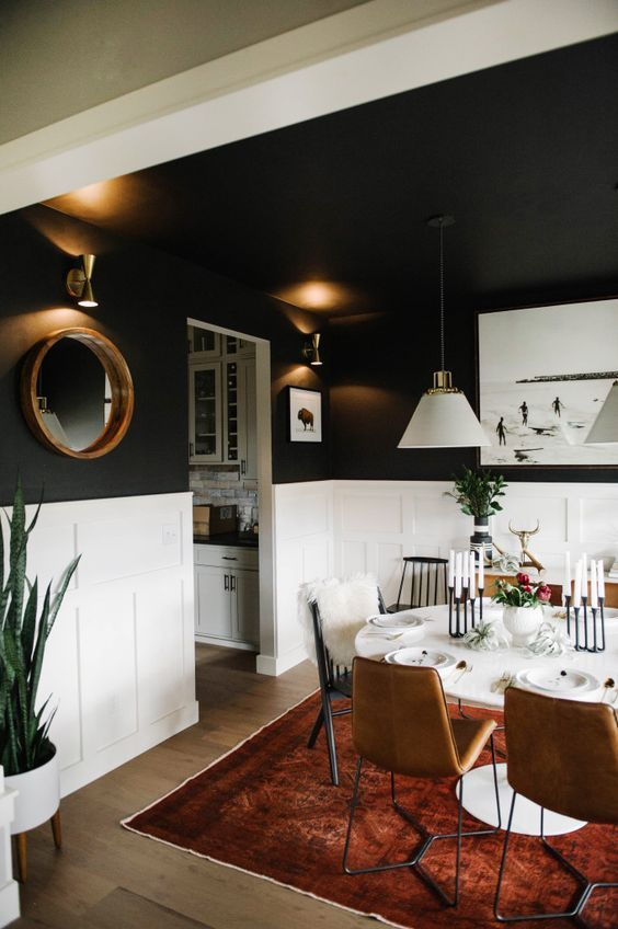 black walls white wainscoting in an eclectic dining room