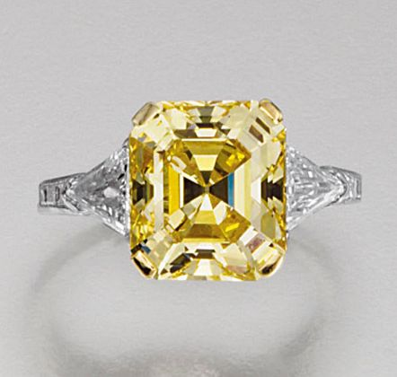 FINE FANCY VIVID YELLOW DIAMOND RING, TIFFANY & CO.  The fancy vivid yellow step-cut diamond weighing 4.55 carats, set between triangular stone shoulders, mounted in platinum,  signed Tiffany.