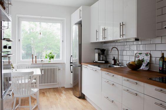 White kitchen, wood countertop, white subway tiles