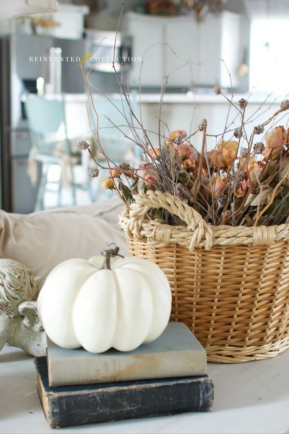 Stacked vintage books and a single white pumpkin shared space with a French basket stuffed with preserved fall flowers for a soft fall style on a sofa table. | Reinvented Collection