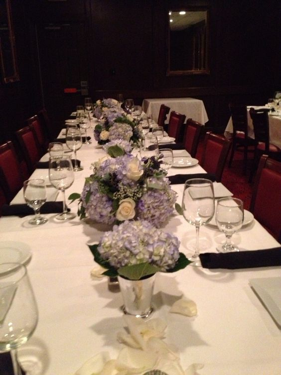 Blue hydrangea in silver tone containers along a long banquet table