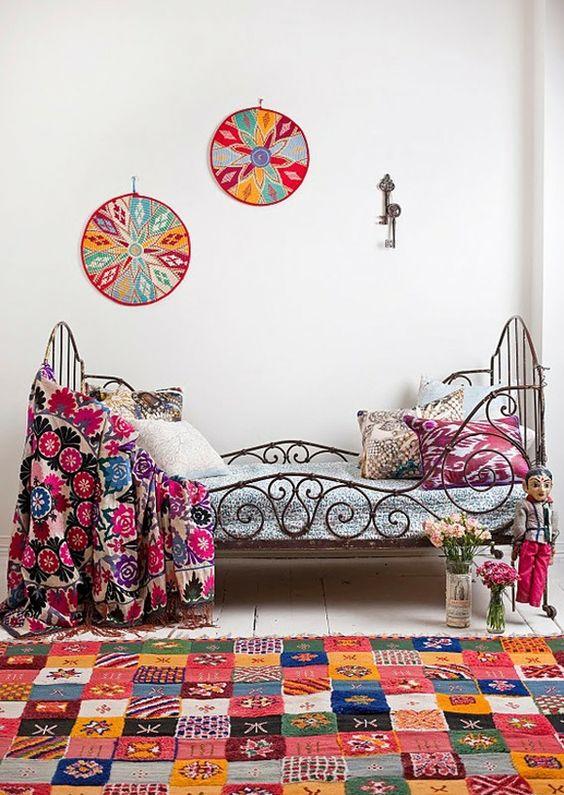 Cama estilo bohemio antigua con ropa de cama y alfombra floreada
