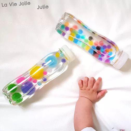 Des bouteilles sensorielles pour bébé, à base d'eau, de pompons, de perles d'eau et... une lampe à huile faite-maison !