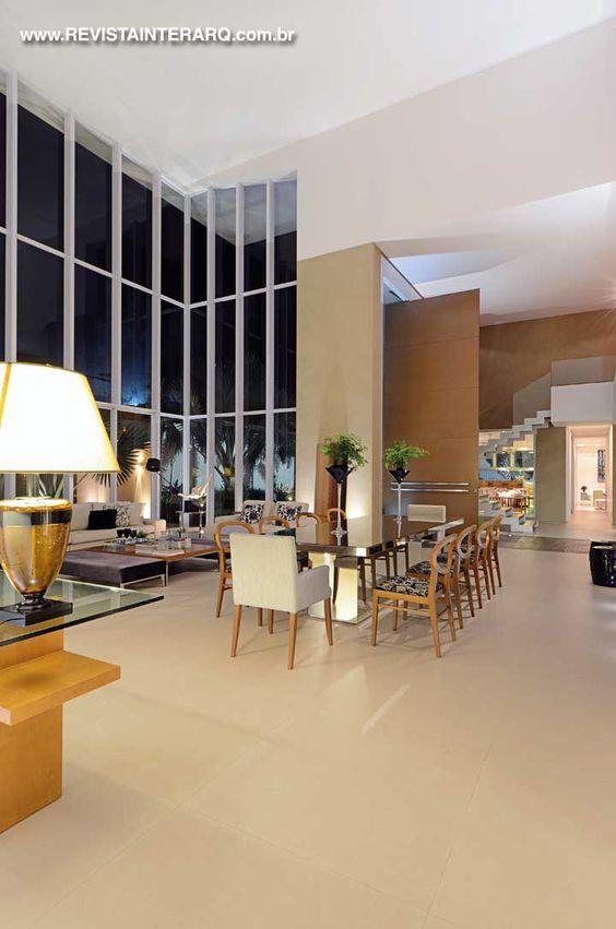 Mesa de jantar espelhada pela Marmoraria e Vidraçaria Avenida. A iluminação técnica é da ViaLight e as telas, do artista Neto Andery
