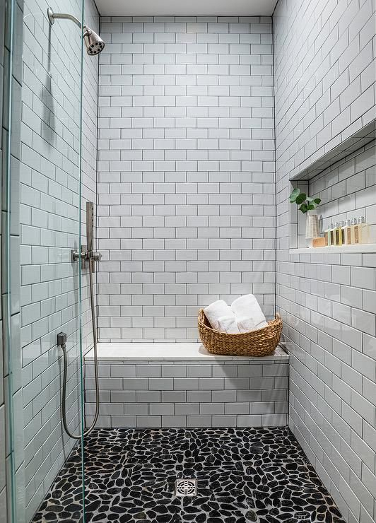 Black River Rock Tiles Accent A Walk In Shower Boasting A White Subway Tiled Bench And White Su In 2020 White Subway Tile Shower River Rock Bathroom Stone Shower Floor
