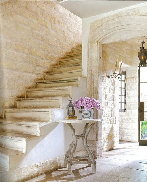 French Country interior design in this entry and staircase. Romantic mood and French farmhouse style with reclaimed stone from Chateau Domingue. #frenchfarmhouse #interiordesign #frenchcountry #staircase #limestone #chateaudomingue #pamelapierce #entryway #oldworld #stonewalls #rusticdecor #rusticelegance