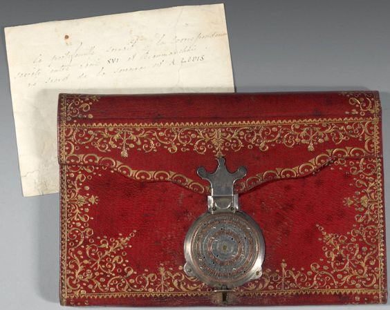 "Wallet belonging to Louis XVI, used for secret correspondence with secret agent Beaumarchais. Red morocco leather, gilt shackled foliage; inside covered with green silk. Combination lock in white and pink gold, composed of six circular dials engraved with letters. To open, align the letters ""A - L - O - U - I - S"" from the center. Beaumarchais oversaw covert supply of arms and financial assistance before France's formal entry into the American War of Independence in 1778.:"