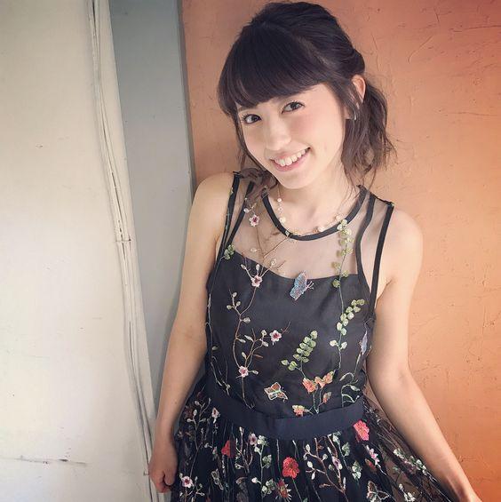 お花が描かれた黒い服の逢田梨香子