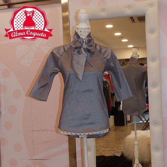 Blusa con manga 3/4, en color plata, com adorno de lazo al cuello. Ideal para…