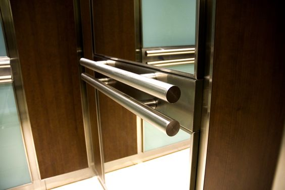 Double Stainless Steel Tubular Handrails Anchored off a Matching Stainless Support Band Adds a Robust Element to this Elevator Interior Design.