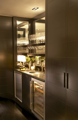 Sleek modern wet bar with espresso cabinetry. The bar area is flanked by cabinets, it features a mirrored interior and espresso stained floating shelves for glasses. A built-in mini fridge and glass fronted wine fridge sit below the counter. A black countertop is paired with an undermount bar sink and polished nickel faucet.  Paul Davis - New York