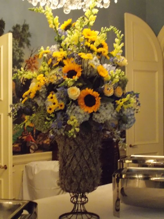 WE CAN USE THE RUCTIC URNS WITH A SUNFLOWER ARRANGEMENT OR CAN DO SUNFLOWERS AROUND BASE AND CURRLY WILLOW