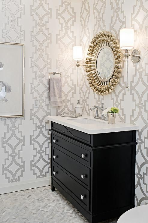 Elegant contemporary powder room is clad in gray trellis wallpaper and features a round chrome balls mirror fixed between Hudson Valley Lighting Gordon Sconces above a black dresser-like washstand accented with square polished nickel knobs and a white quartz countertop.
