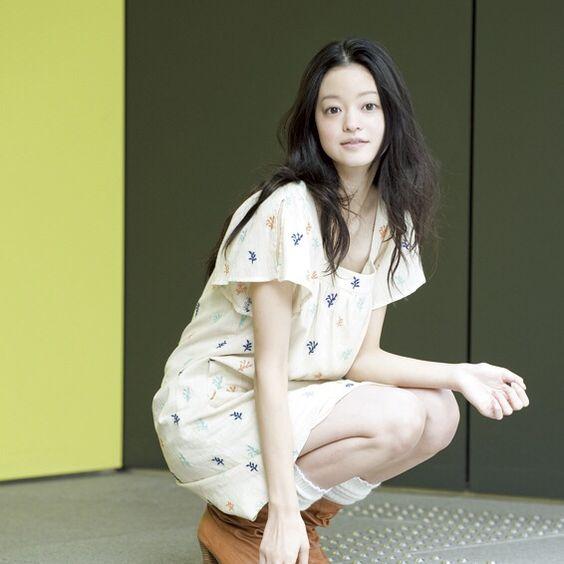 ワンピースを着てしゃがんでいるワンレンの小林涼子の画像