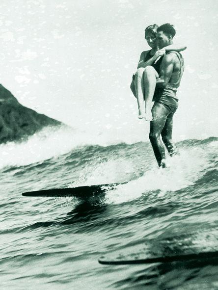 カップルがサーフィン