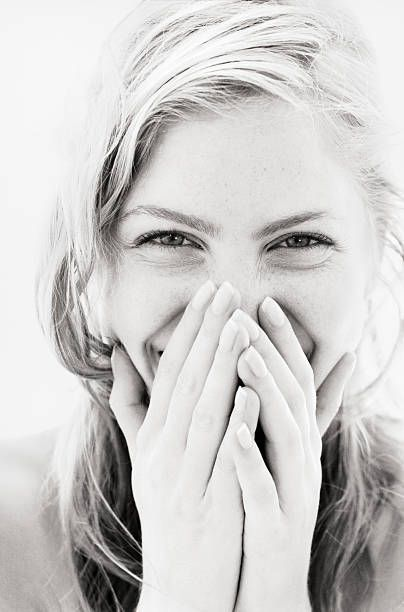 Young woman laughing, hands over mouth, close-up, portrait (B&W) | Photos.com