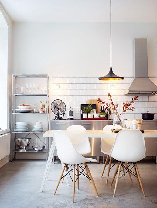 concrete floor, half wall white tiles, metallic storage, in a bright open concept kitchen