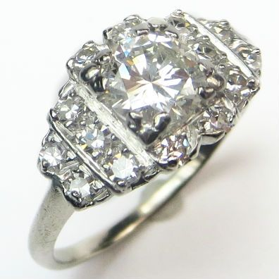 Shimmer Queen: A dazzling center diamond holds court above a shimmering panel of tiny sparklers complete with just enough Art Deco flair.  Ca.1935. Maloys.com
