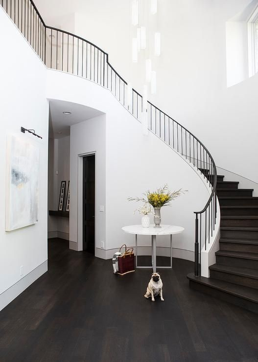 A Round Marble Top Foyer Table Sits On An Ebony Wood Floors In An Elegant Foyer Boasting A Gray Abstract Art Pic Foyer Decorating Round Stairs Curved Staircase