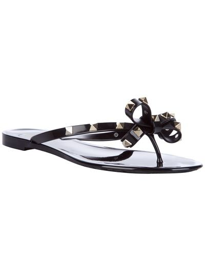 Black plastic sandals from Valentino featuring a toe thong strap, a bow detail to the front and metallic stud detail at the straps.