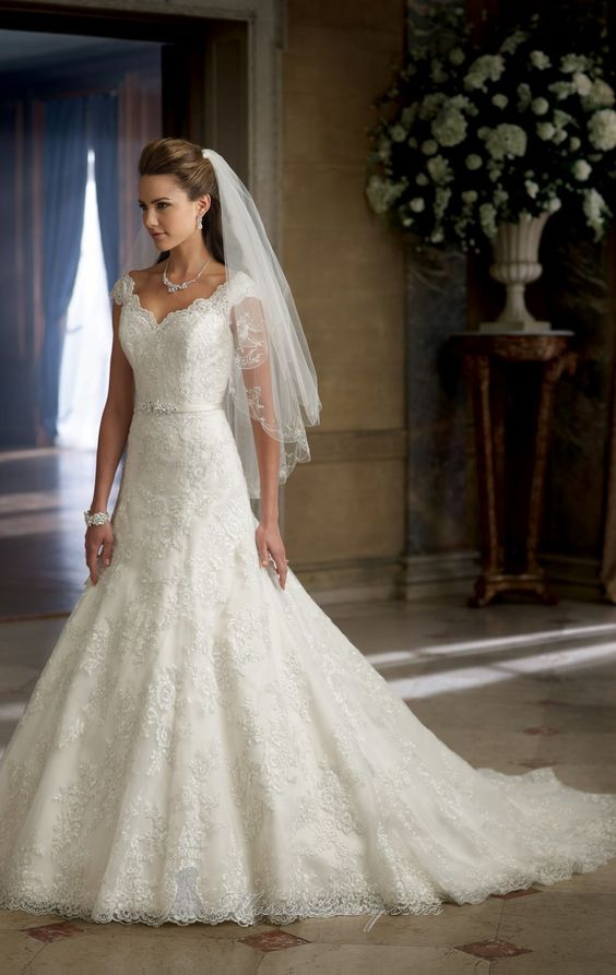 Embellished Scalloped V Neckline Gown by David Tutera   Item #213253 by David Tutera (Fall, 2013)        $1,685.00  Exhibit your radiance on the best day of your life in David Tutera 213253. This beautiful wedding gown is made of lace, tulle and organza. The fitted bodice features a scalloped v neckline with cap sleeves and scalloped v back design. A jeweled band adorn the natural waist while the scalloped hemline extends to a chapel train.