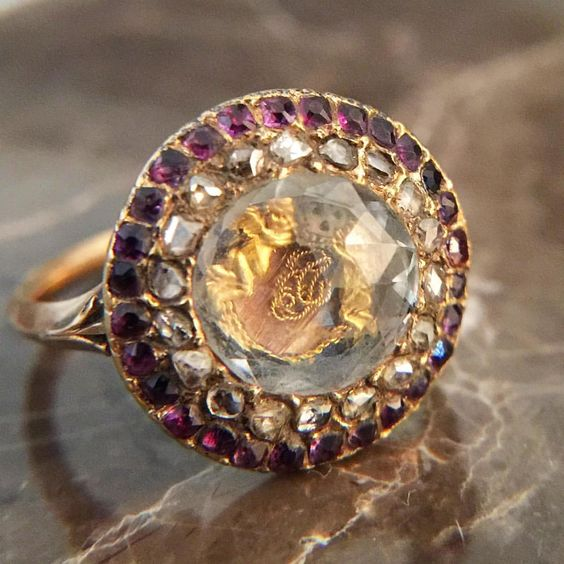 A beautiful Georgian era Stuart Crystal Ring with cherubs and skull under rock crystal surrounded by a halo of diamonds and another of amethysts.