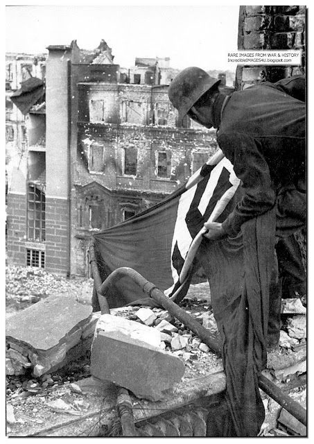 A German soldier fastens the Nazi flag onto a building in Stalingrad. October 1942
