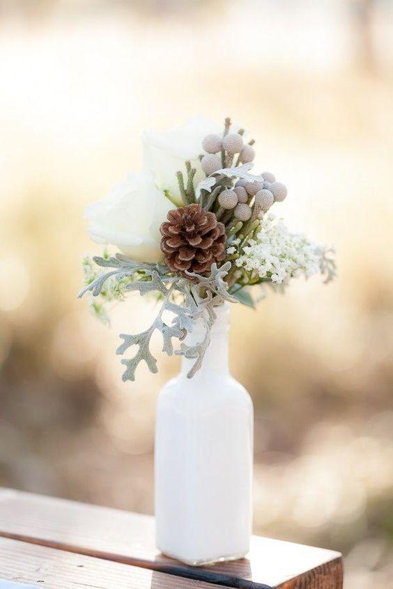 On révolutionne le bouquet de table avec des touches d'hiver : une pomme de pin, un vase blanc