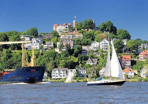 Schiffe auf der Elbe vor Hamburg Blankenese - Frachtschiff und Segelboote in Fahrt; Süllberg mit Turm und Hamburgflagge.