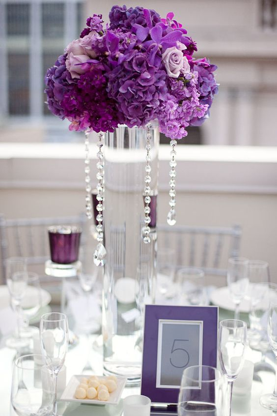 Decoração com arranjos altos de flores na cor púrpura e contas de cristal.