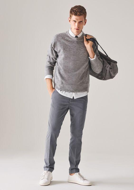 Acheter la tenue sur Lookastic: https://lookastic.fr/mode-homme/tenues/pull-a-col-rond-chemise-de-ville-pantalon-de-costume/19910   — Chemise de ville blanche  — Cravate noir  — Grand sac en toile gris  — Pull à col rond gris  — Pantalon de costume gris  — Baskets basses en cuir blanches