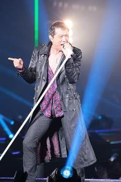 黒のロングコートを着て熱唱している矢沢永吉の画像