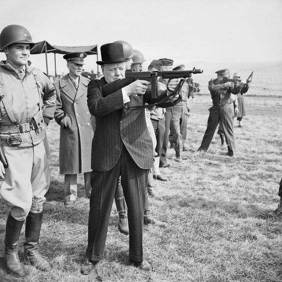 """Shortly before the Normandy invasion, Winston Churchill tests his hand with the Thompson sub-machine gun in .45 caliber. The """"Tommy Gun"""" was by then the standard light automatic weapon of the US Army and in extensive use by the British and Canadian armies. In the background, General Eisenhower also takes aim with the same gun."""