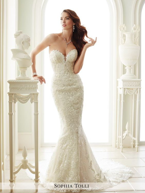 Strapless soft tulle over sequin tulle sheath adorned with allover hand-beaded lace appliqués, plunging sweetheart neckline with illusion panel