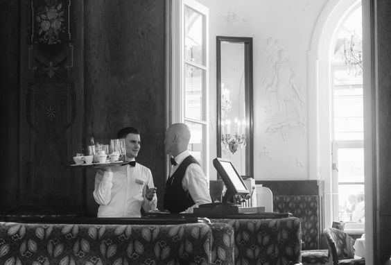 Waiters exchange a quiet word at the old landmark Cafe Landtmann in Vienna - Austria - Ringstrasse on the old quarter.